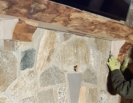 Photo of fitting a live edge corbel in place under a mantle