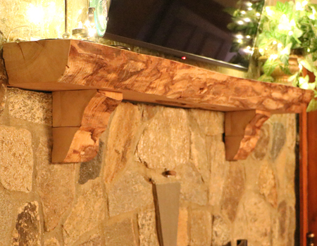 Close Photo of a Live Edge Curly Maple Mantle on a stone fireplace.