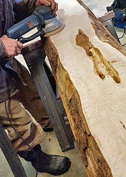 Photo of man sanding the face of a live edge slab